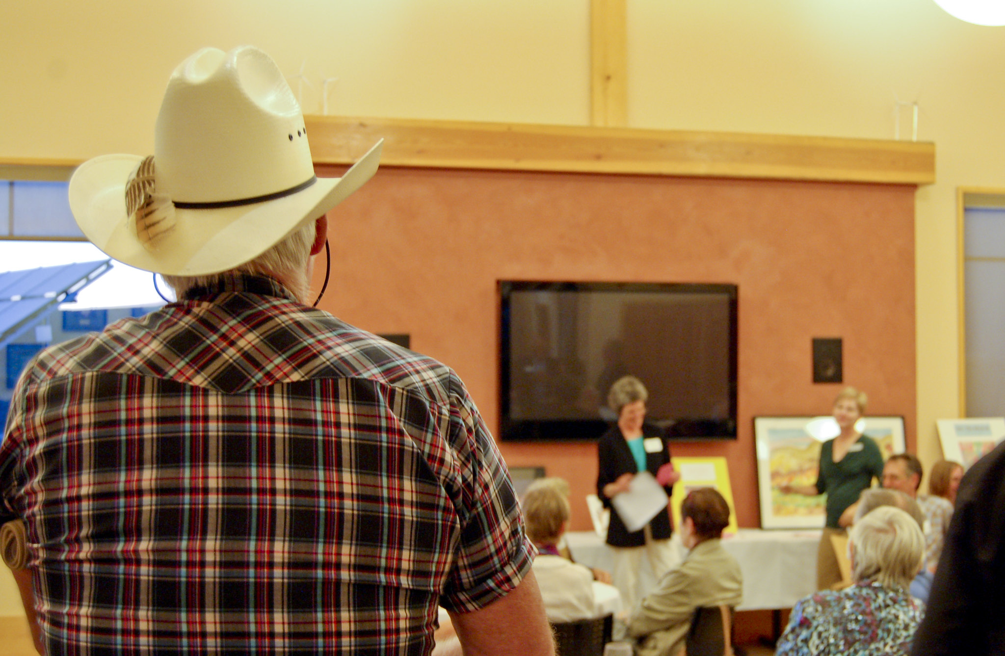 A community member listens to a PSE employee give a speech.